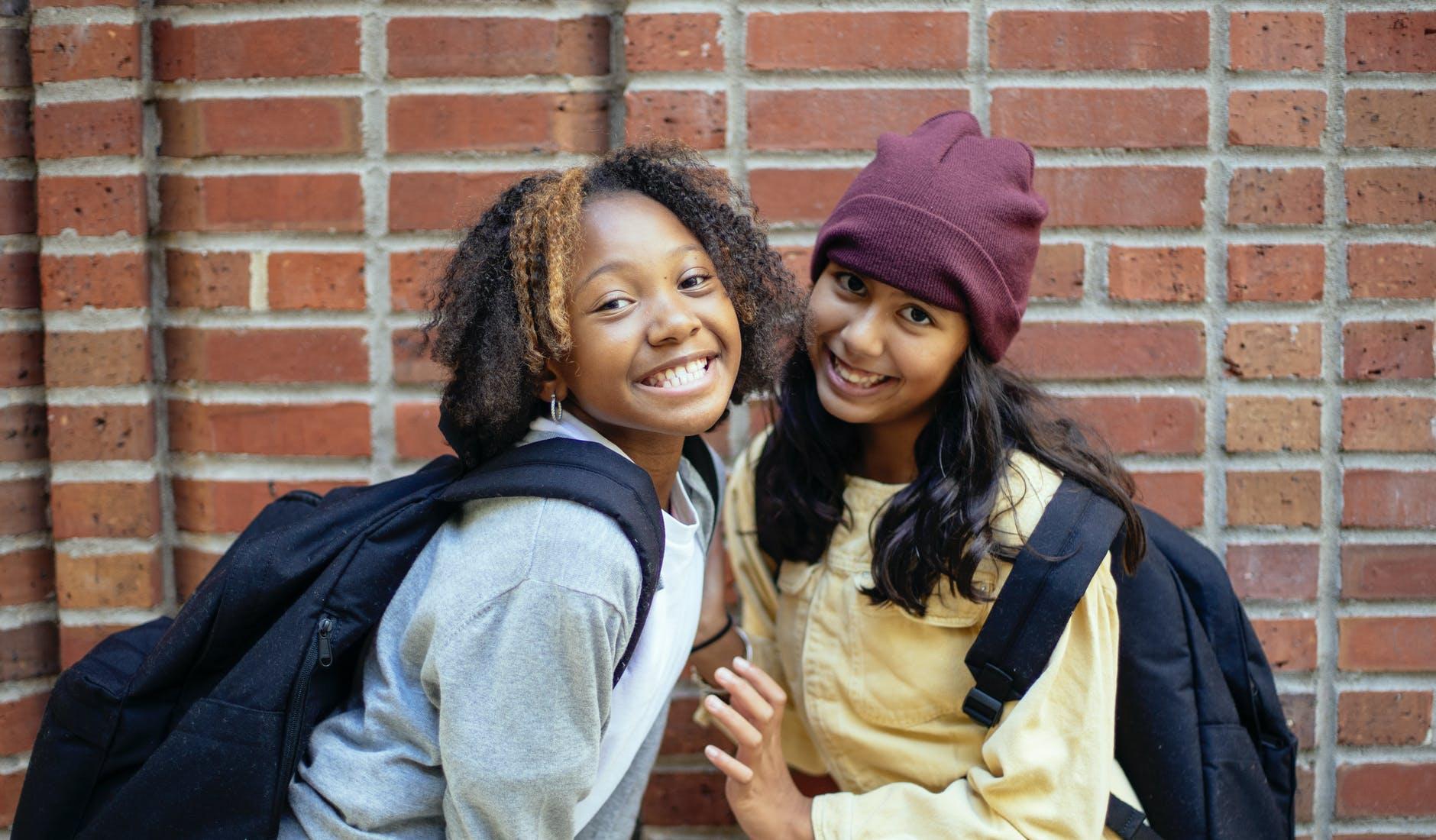 smiling diverse schoolgirls with rucksacks near brick wall
