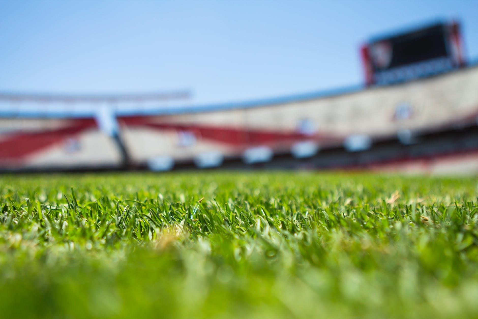 green grass across beige red open sports stadium during daytime