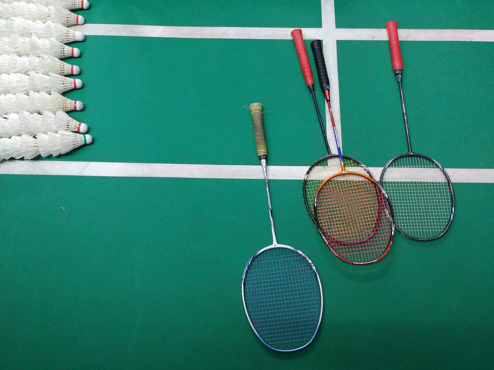 green and white court with badminton rackets